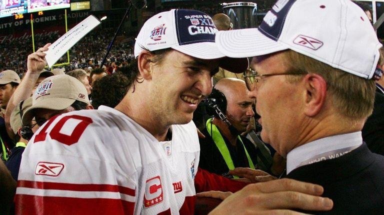 Eli Manning celebrates with co-owner John Mara after
