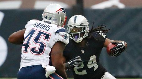 Raiders running back Marshawn Lynch rushes against Patriots