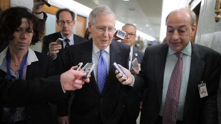 Senate Majority Leader Mitch McConnell talks with reporters