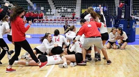 Connetquot's girls volleyball team celebrates after beating