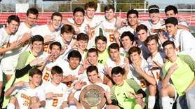 Chaminade's soccer team surround the championship trophy after