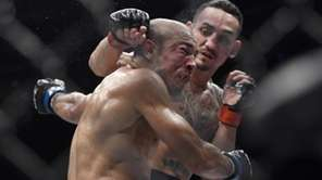 Max Holloway, right, punches Jose Aldo, of Brazil,