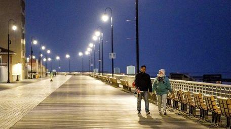 A couple strolls on the boardwalk in Long