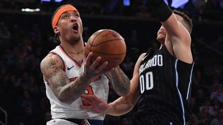 Knicks forward Michael Beasley is defended under the