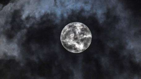 A supermoon briefly breaks through the clouds over