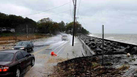 Ocean water crashes onto the road near Asharoken