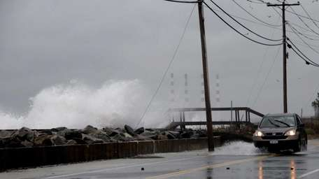 Waves crash on the roadway near Asharoken Beach