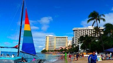 Surfers and a sailboat crowd popular Waikiki Beach,