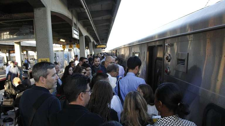 Commuters pile into a morning train at the