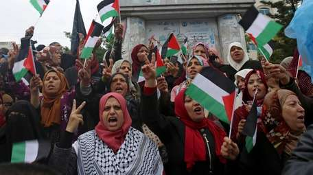 Women hold Palestinian flags and chant slogans during