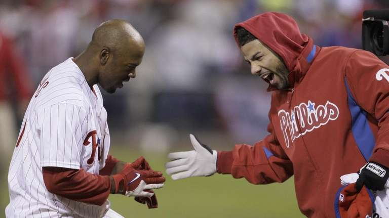 Philadelphia's Jimmy Rollins high fives with J.C. Romero