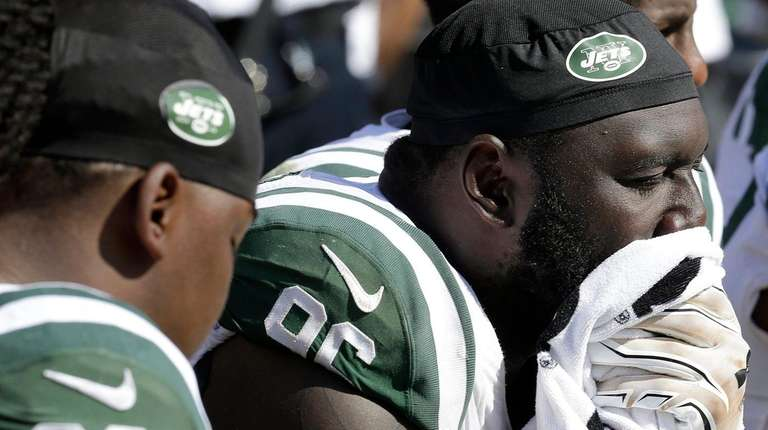 Jets defensive end Muhammad Wilkerson, right, sits on
