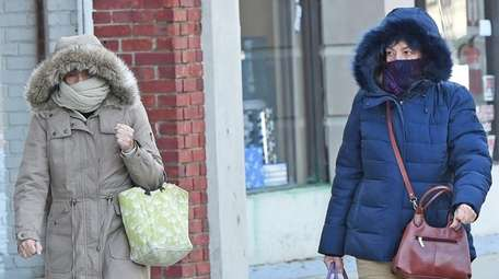 Two women are bundled up as they walk