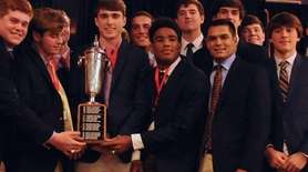 Garden City teammates gather around the Rutgers Cup,