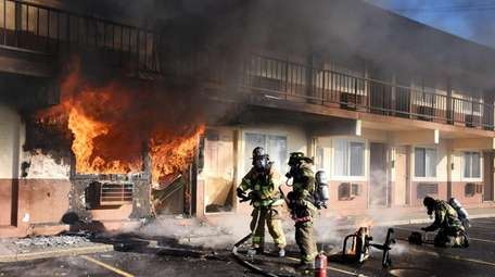 Firefighters battle a blaze at the Olympic Motor Lodge