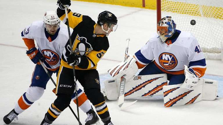 Penguins' Jake Guentzel redirects a shot by Kris