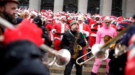 A man plays a saxophon as a crowd
