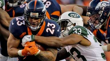 Broncos running back Devontae Booker is hit by
