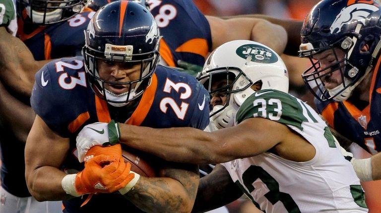 Broncos running back Devontae Booker is hit by