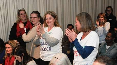 Parents from Long Island applaud during a state