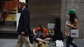 A man plays his guitar while panhandling on