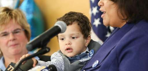 Nicholas, 29 months, reaches for a microphone as
