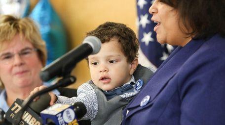 Nicholas, 29 months, reaches for a microphone as
