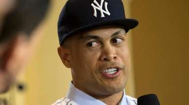 New Yankee Giancarlo Stanton talks with reporters during