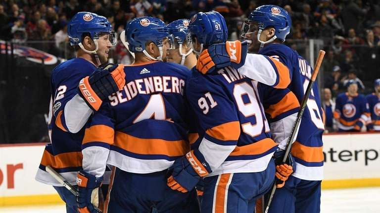 Islanders players celebrate a goal by John Tavares