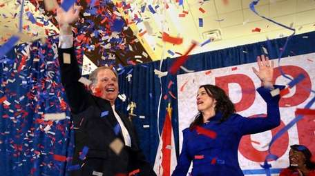 Democrat Doug Jones and his wife, Louise, wave