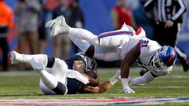Cowboys quarterback Dak Prescott slides under Giants safety