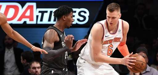 Knicks forward Kristaps Porzingis is defended by Nets