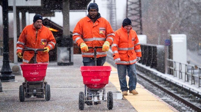 LIRR employees spread salt at the Baldwin station
