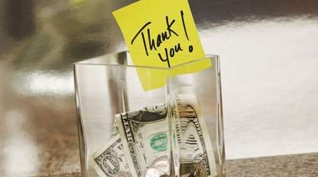 Glass tip jar with a thank you note.