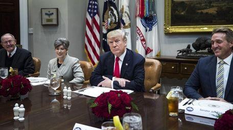 President Donald Trump -- flanked by Sens. Lamar