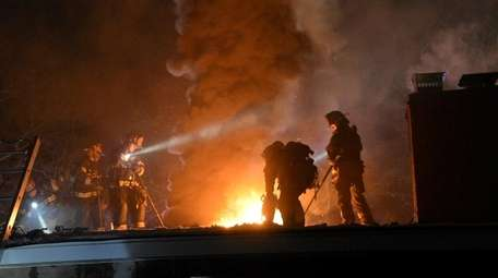 Firefighters on the roof of a house in