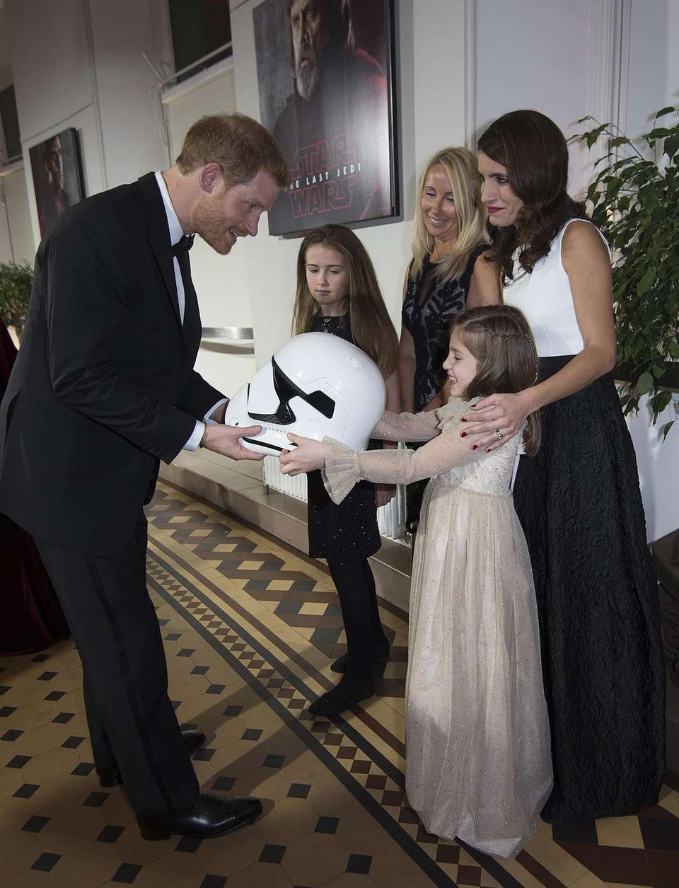 Prince Harry is handed a Stormtrooper helmet by