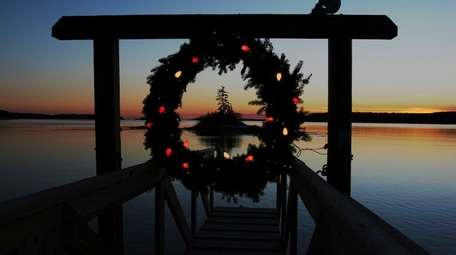 A Christmas wreath decorated with lights hangs at