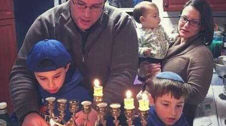 Adam and Jordana Rothschild light the menorah in