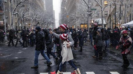 A pedestrian uses a selfie stick to take