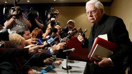 Cardinal Bernard Law departs a news conference during