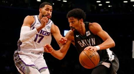 The Nets' Spencer Dinwiddie drives against the Kings'