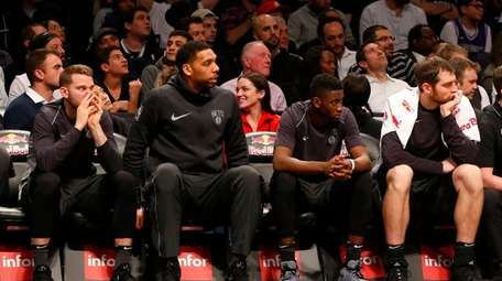 The Brooklyn Nets bench looks on late in
