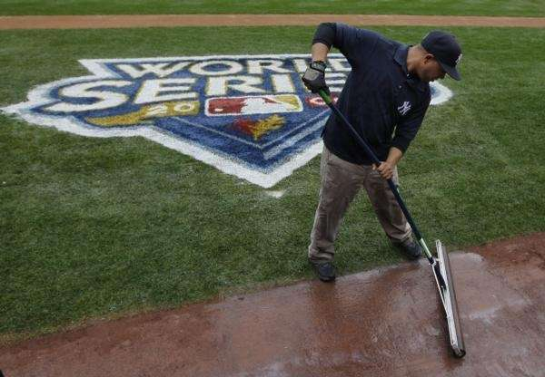 Angel Nunez squeegees water off the infield warning