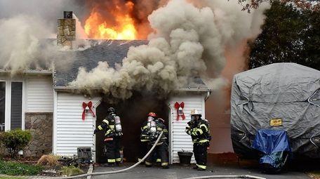 Firefighters battle a Farmingville house fire on Friday,
