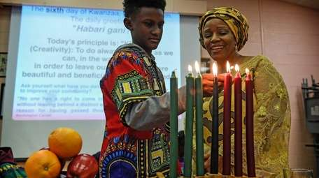 Pamela Allen and Quintel Harris, 11, light the