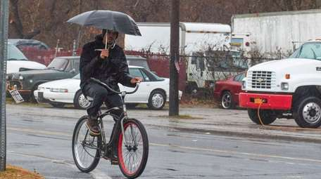 A man rides his bicycle in the rain