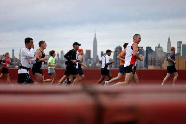 Runners pass over the Pulaski Bridge from Brooklyn