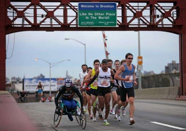 A runner pats a wheelchair competitor on the