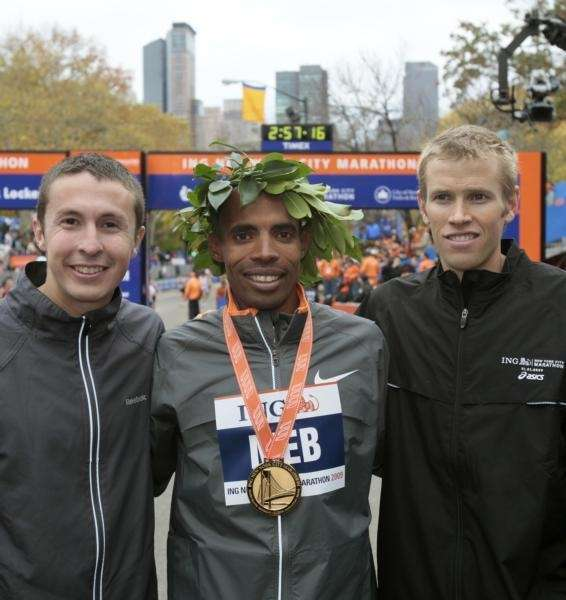 Men's marathon winner Meb Keflezighi, center, poses with